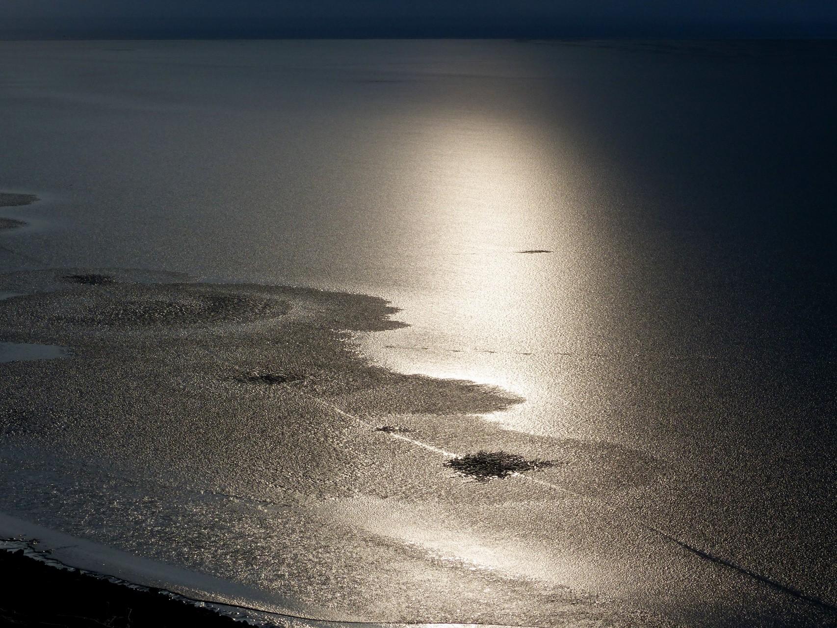 Die aufgehende Sonne spiegelt sich im dünnen Eis des See's