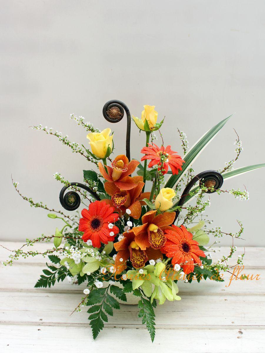 オレンジのガーベラと黄色のバラ、シンビジウムとゼンマイのアレンジメント