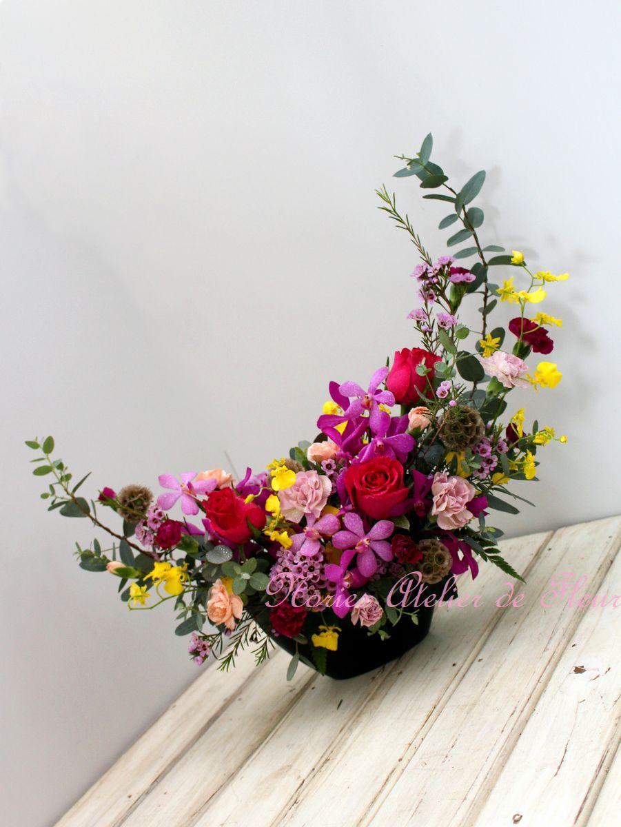濃いピンクのバラとランを使った三日月型のアレンジメント