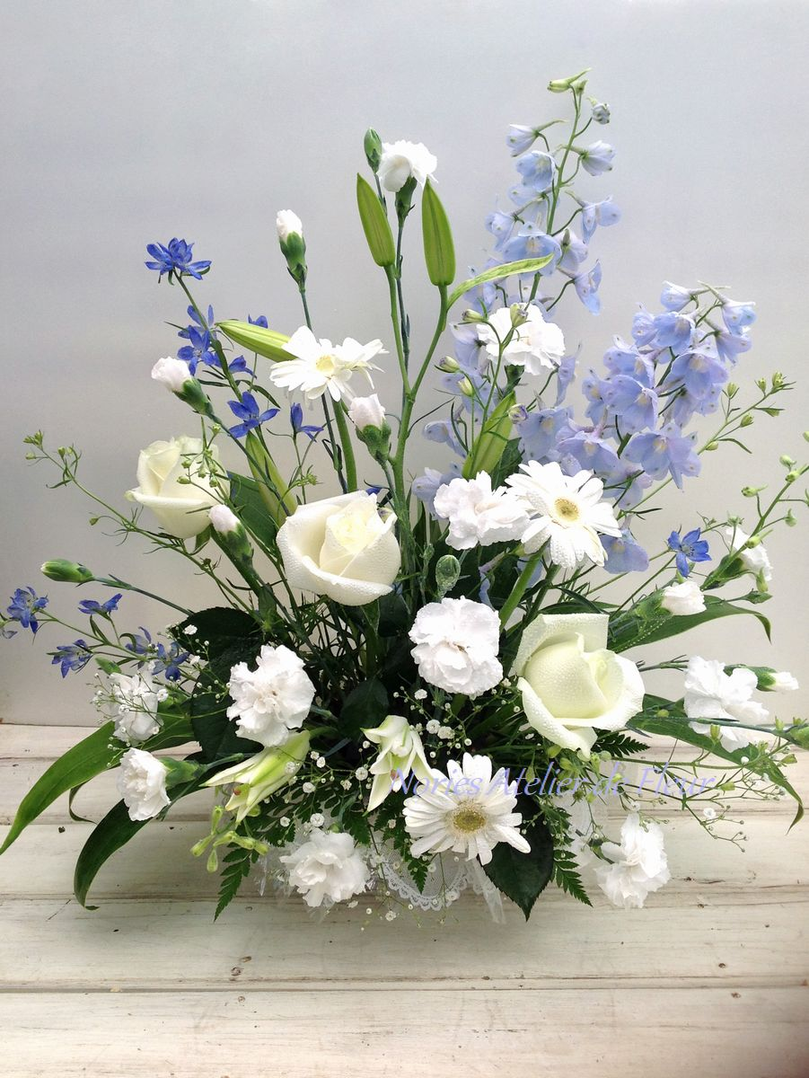 淡いブルーのデルフィニウムを加えたお悔やみの花