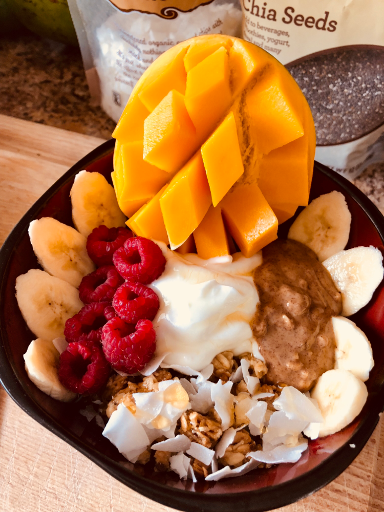 Self-made Açaí Bowl, decorated with my favorite toppings: raspberry, coconut chips, banana, mango, honey granola, mango, raw almond butter and Greek yogurt.