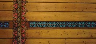 Die blaue, masswerkverzierte Längsbahn kreuzt die rote, mit Flachschnitzereien versehene Querbahn.