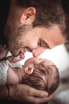 Newborn Baby Shooting von einem Vater der sein Kind hält Nase an Nase fotografiert von der Schweizer Familien Fotografin Monkeyjolie