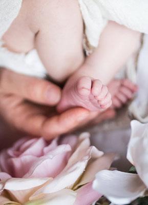 Baby liegt auf einem weisses Tuch man sieht die kleine Füsse fotografiert von der Familien Fotografin Monkeyjolie in Szene gesetzt