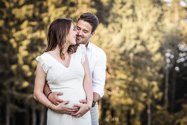 Schwangerschafts Shooting im Bohemien Style in weissem Sommer Kleid Sie hält ihren Bauch und er steht hinter Ihr fotografiert von der Familien Fotografin Monkeyjolie