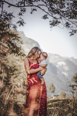 Familien Fotografie Mutter hält ihr Kind vor einer Bergkulisse in Szene gesetzt von der Familien Fotografin Monkeyjolie in Appenzell