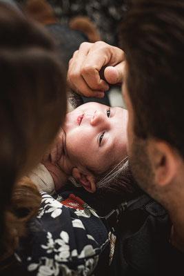Newborn Shooting Eltern sitzen im Wohnzimmer auf der Couch mit Baby auf dem Schoss fotografiert von der Schweizer Familien Fotografin Monkeyjolie