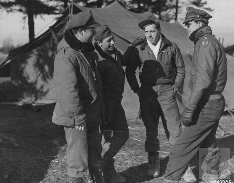 Belgium 1944, Talking over a mission in front of the captured German tents that are used for operations and orderly room are, 2nd Lt. Coleman F. Cody, S/Sgt Herbert Young, S/Sgt Michael J. Parliscak and Capt. Fred A. Campbell. Picture National Archives