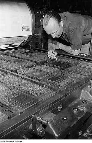 A classic image of a printer inspecting the set and 'locked up' pages (or 'the forme')