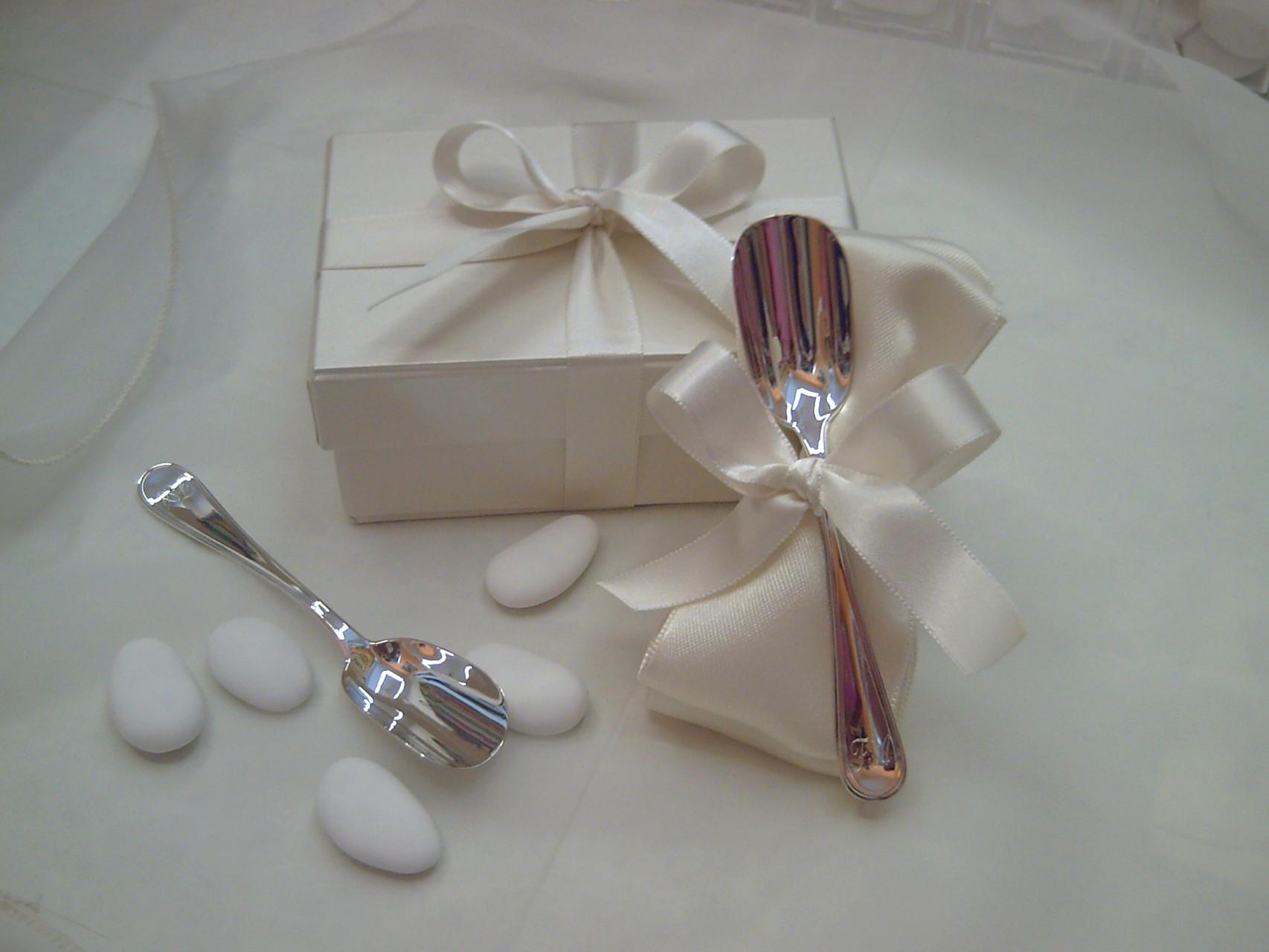 Un nastro di raso piegato forma un fiocco con i confetti e fa da base al cucchiaino d'argento nella scatolina su misura