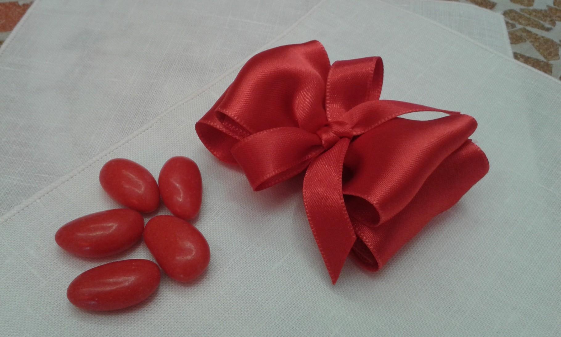 Il nastro di raso, piegato a formare un doppio fiocco contiene i confetti rossi