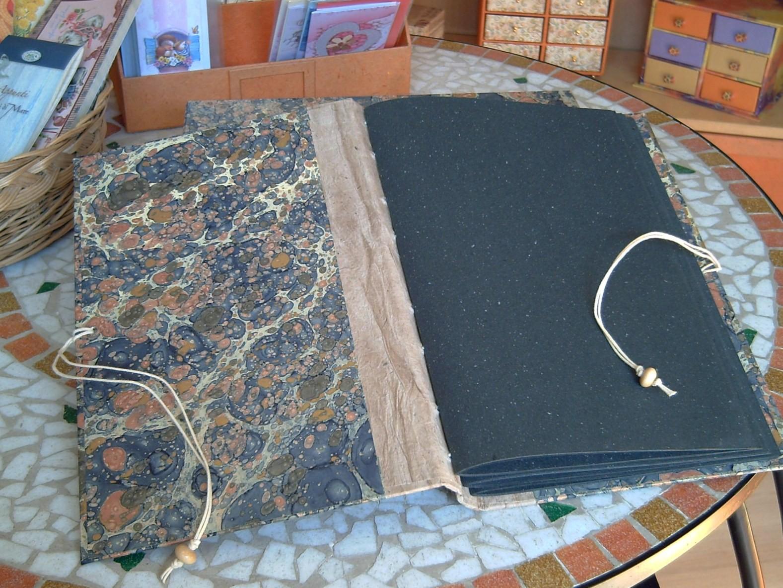 Album composto da tre fascicoli di cartoncino riciclato nero cuciti a vista sul dorso flessibile formato da liste di cartone