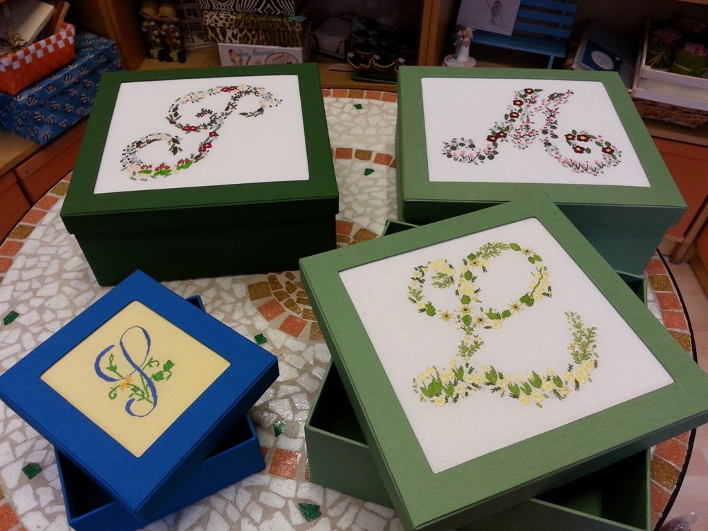 Eleganti scatole su misura in tela con coperchio a cornice valorizzano questi preziosi ricami del cliente