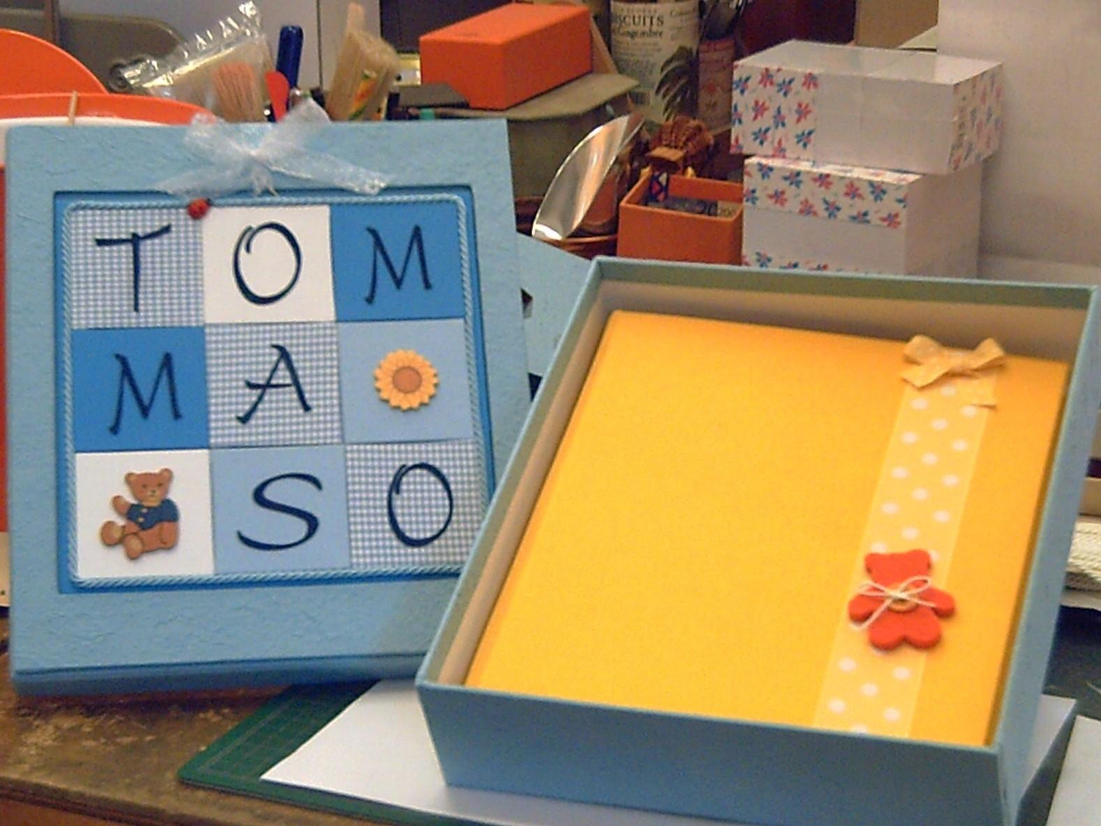 La scatola dell'album ha la particolarità di incorniciare il nome del bambino su un pannello che può essere appeso