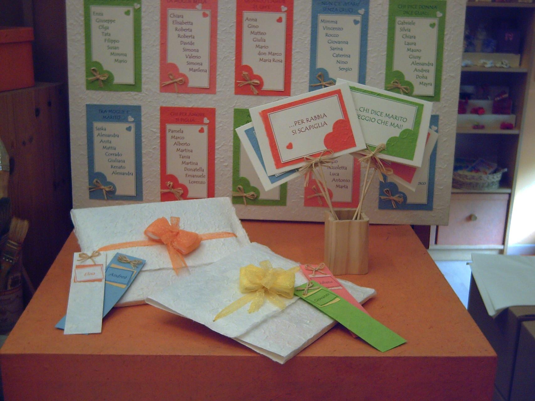 In primo piano i cartelli per i tavoli, alcuni segnalibri usati come segnaposto e la confezione della bomboniera che in questo caso è un libro