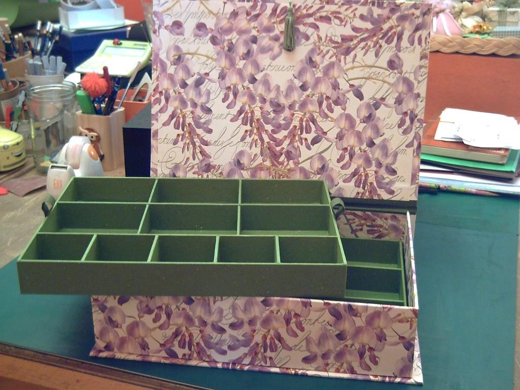 Dettaglio della scatola aperta: entrambi i ripiani del doppiofondo sono suddivisi in scomparti di dimensioni diverse