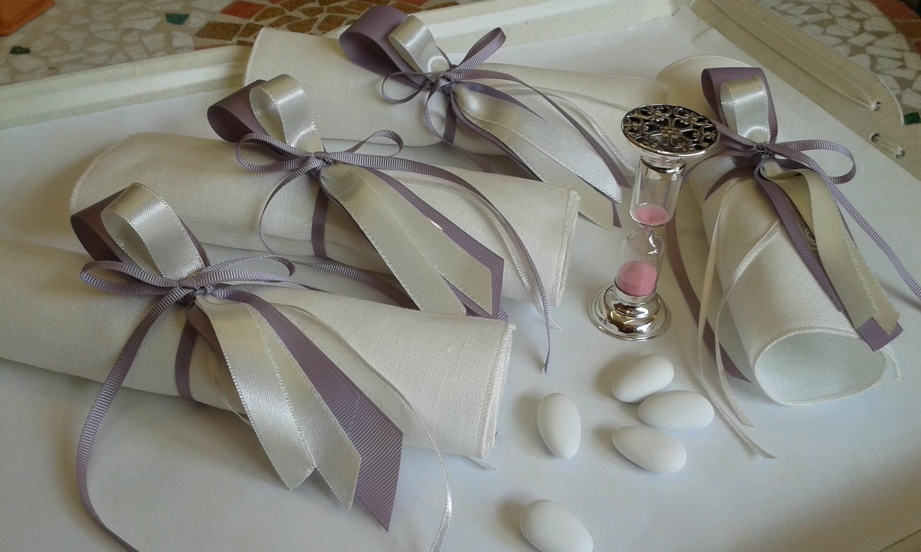 Candidi fazzoletti di lino avvolgono una piccola clessidra dono per gli ospiti della festa (oggetto fornito dal cliente)