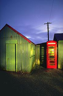 Rote Telefonzelle neben grünen Schuppen, Regenwetter