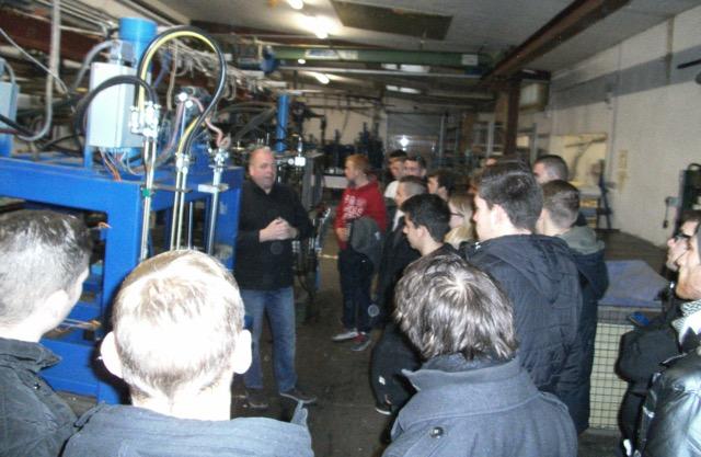 Der technische Leiter der Firma Grumbach, Thorsten Godow, erklärt den Auszubildenden den Vorgang des Einspritzens des PUR-Gemischs in die Formen, wodurch die Dachgullys entstehen.