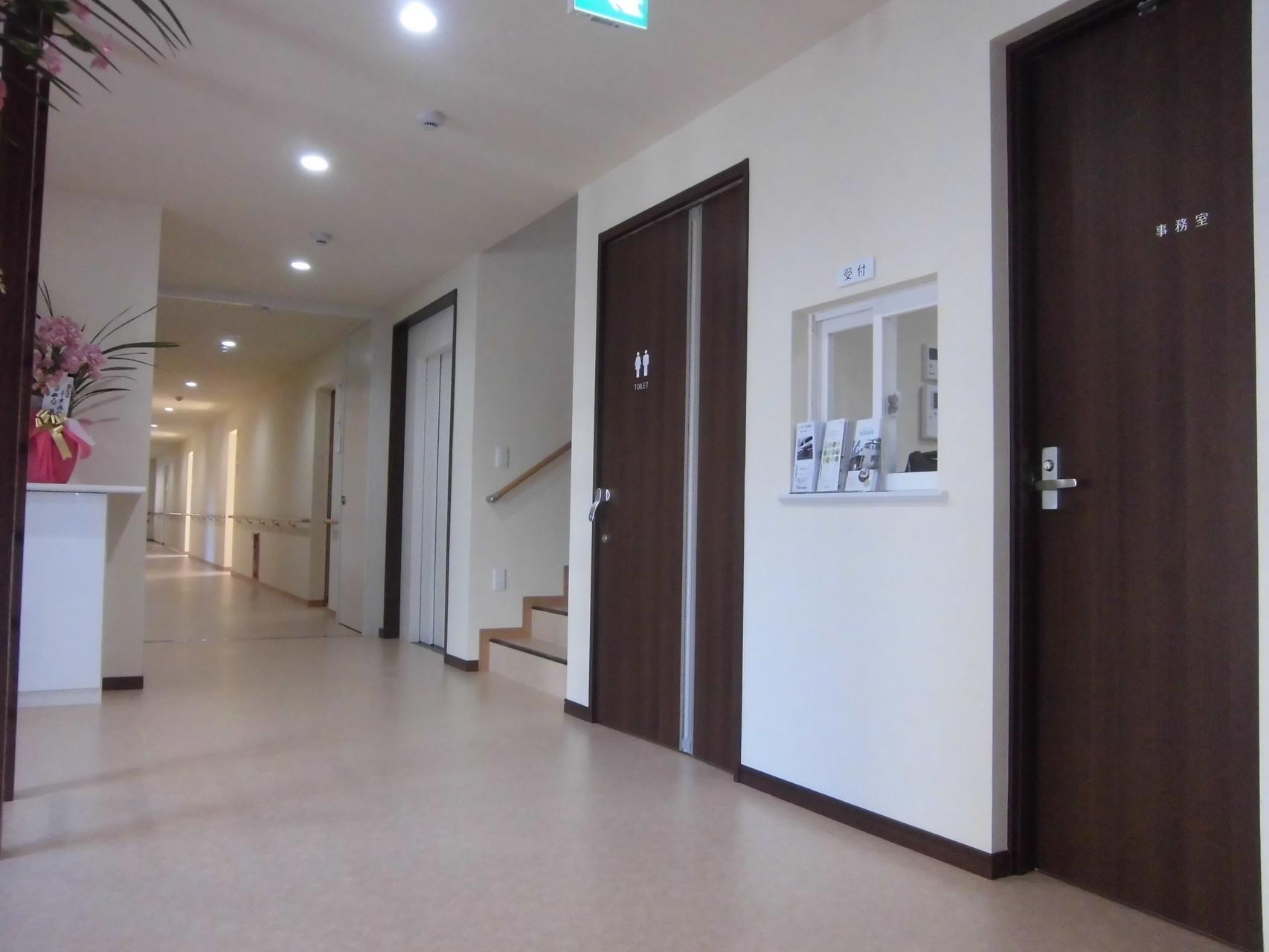 玄関ホール~廊下(手前から事務室、共有トイレ、階段、エレベーター、居室と並ぶ)