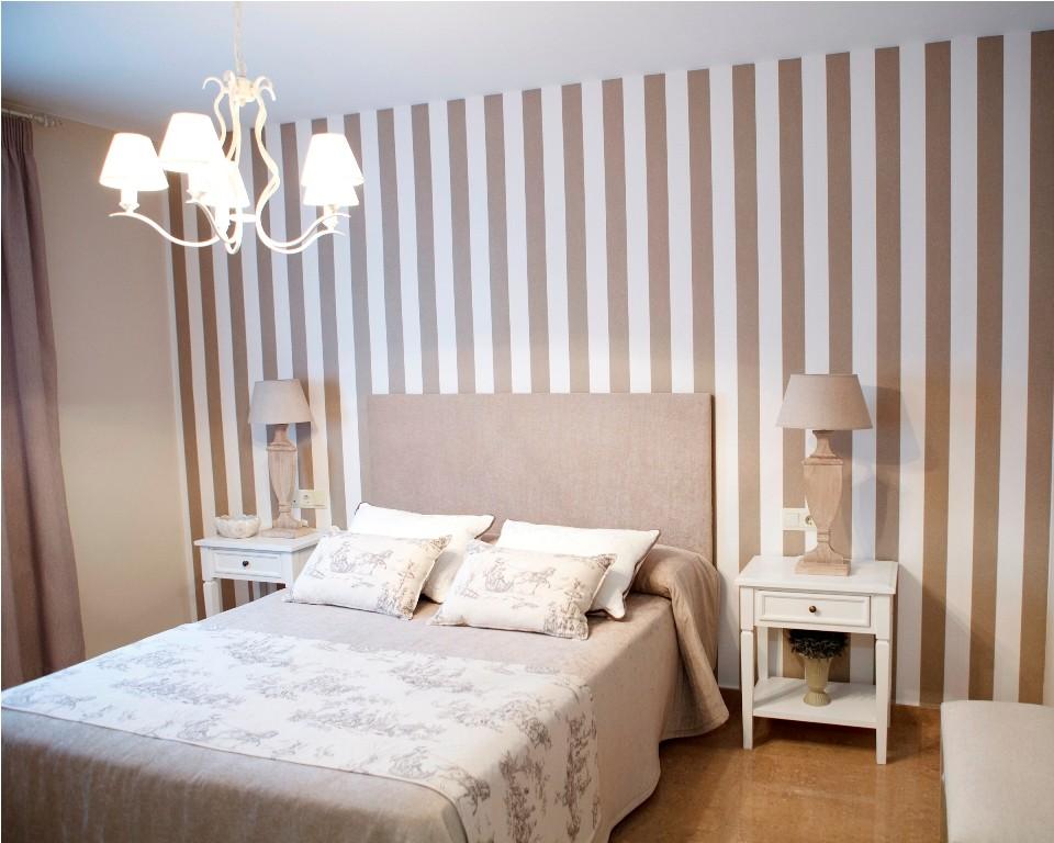 Papel pintado a rayas en color arena en el dormitorio principal