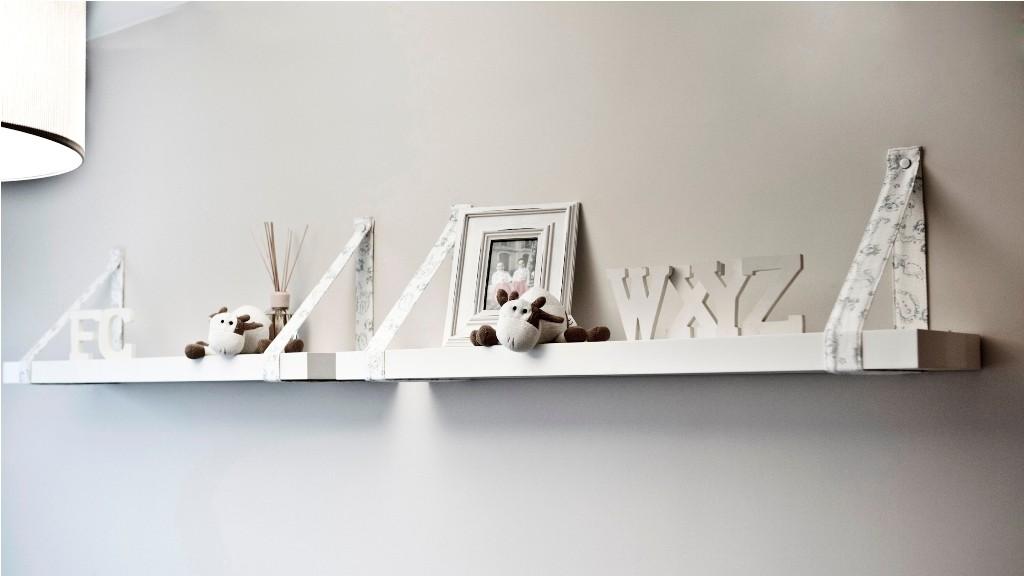 Balda sujeta a pared con tiras confeccionadas igual que la lámpara en el dormitorio infantil