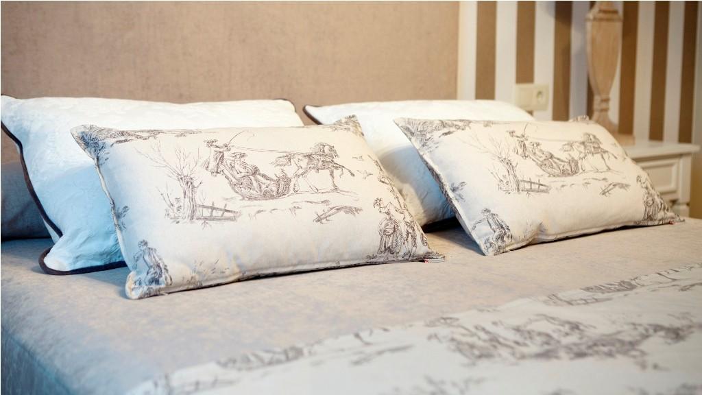 Conjunto de cojines confeccionados a juego con manta de pie en el dormitorio principal