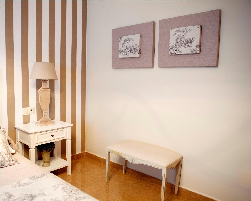 Banqueta tapizada en color arena para el dormitorio principal