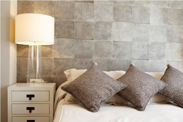 Cojines sobre cama y papel vinílico en el dormitorio principal