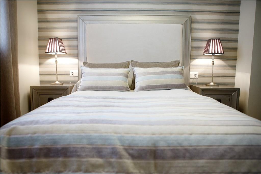 Conjunto de cojines confeccionados a juego con la manta de pie en el dormitorio principal