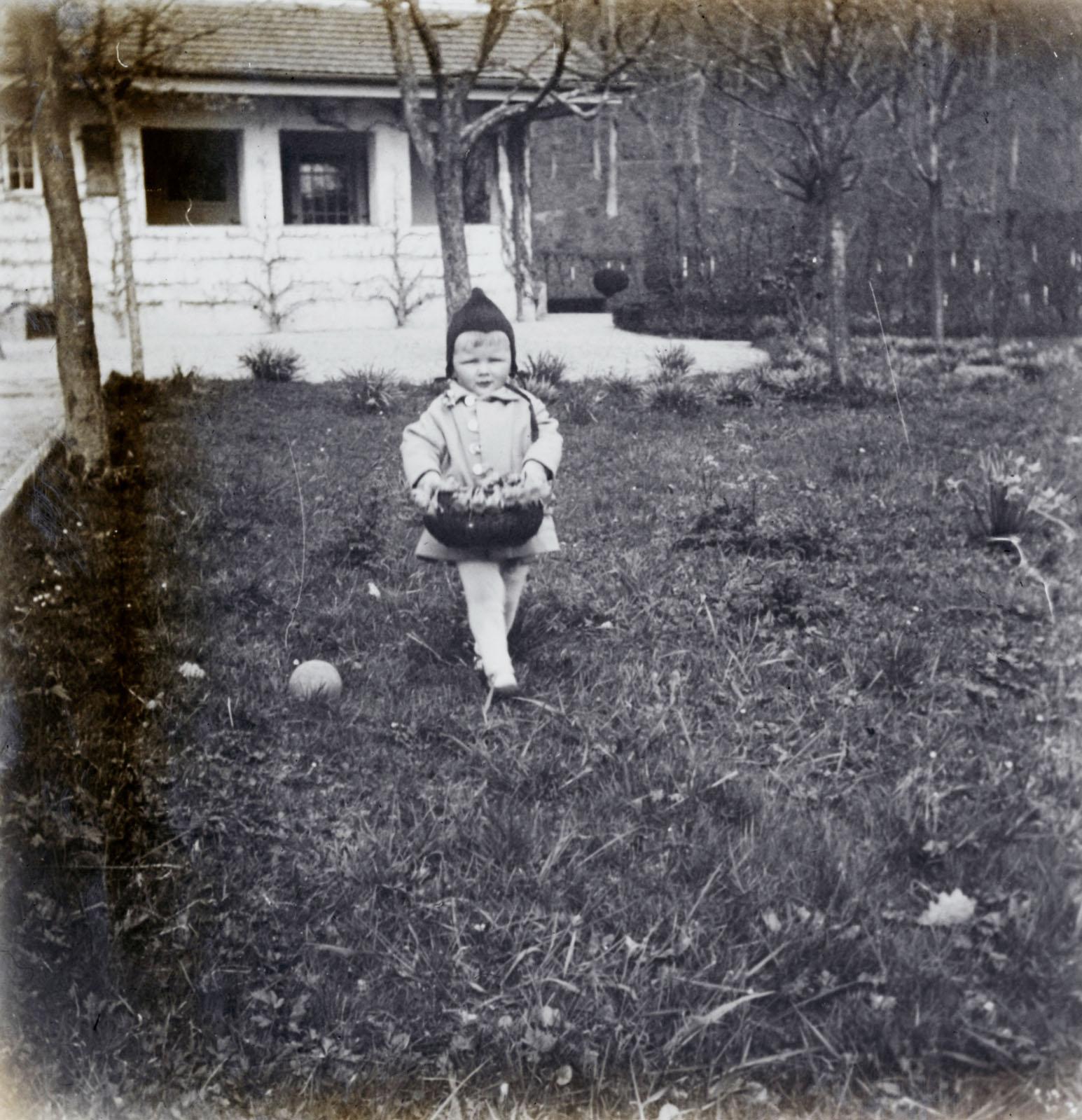 Der kleine Peter Thalmann (Enkel von Cuno Amiet) trägt stolz sein Osternest durch den Garten, 1928