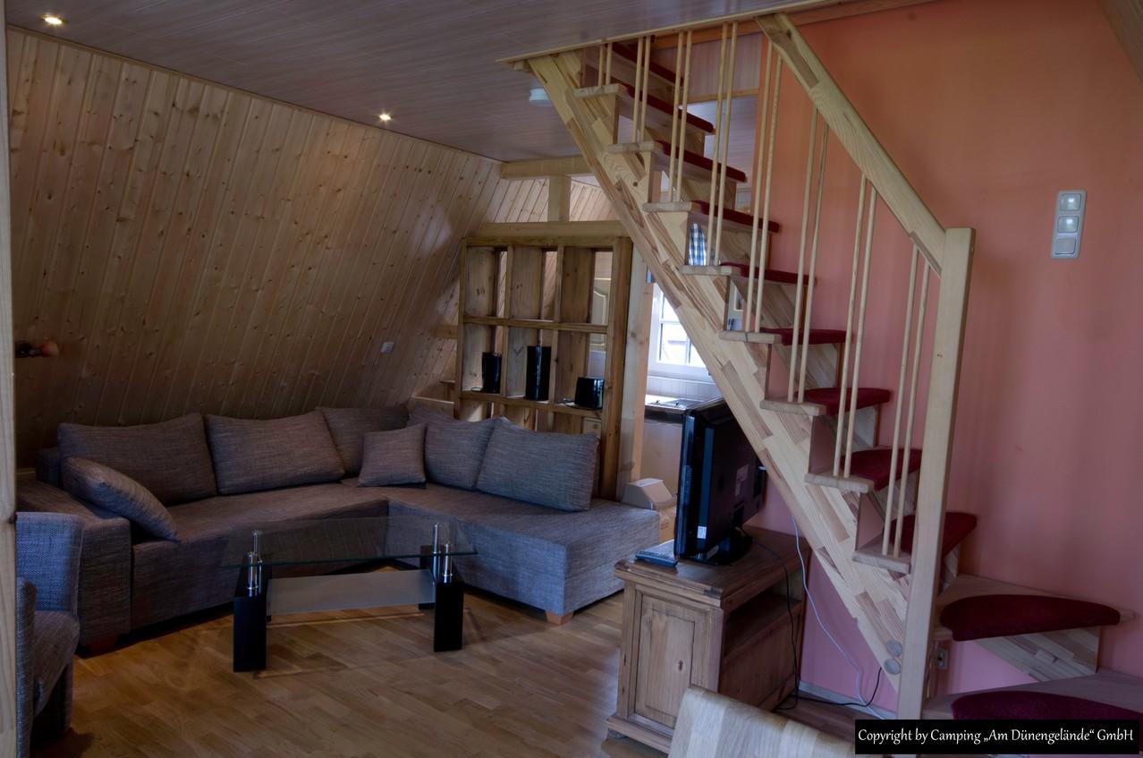 Das Wohnzimmer mit der Einbauküche dahinter