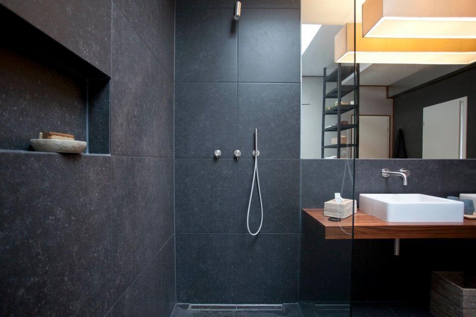 Die großzügige Dusche ist komplett mit Naturstein ausgekleidet.