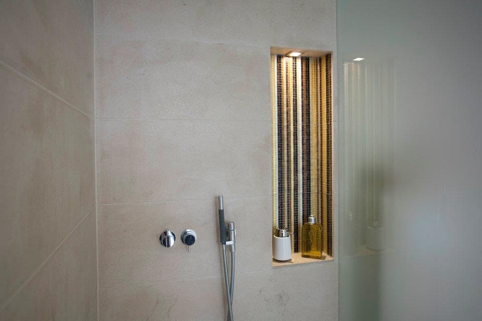 Ein großzügiger Duschbereich mit Stil brechender, beleuchteter Ablagenische.