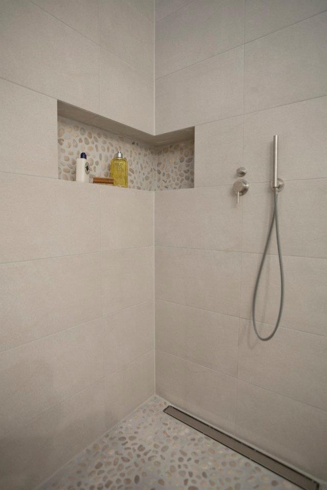 Für das etwas andere Feeling unter den Füßen ist der Boden der Dusche, sowie die Wandnische mit hellen Kieselsteinen ausgelegt.