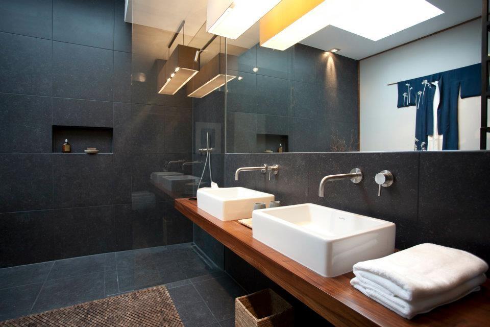 Waschplatz und Dusche sind nur durch eine Glaswand voneinander getrennt.