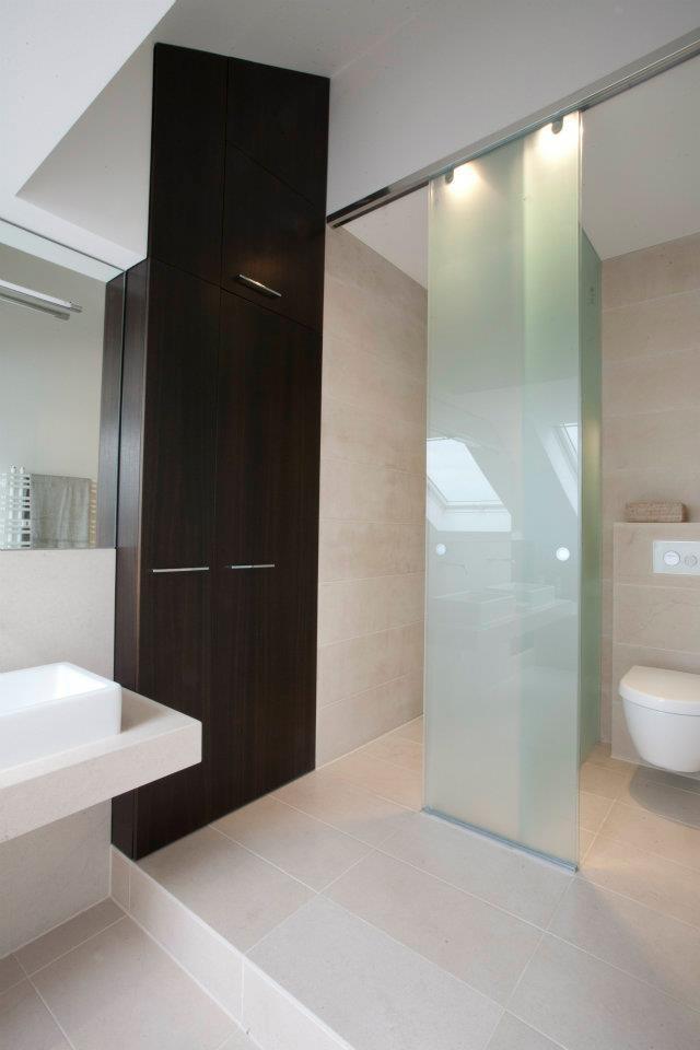 Eine gläserne Schiebewand trennt den Dusch- und WC-Bereich vom Rest des Raumes.