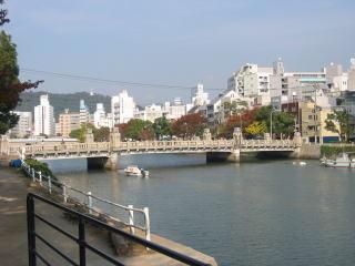 左写真のカフェからの風景。このレトロ調の橋は「京橋」と言い、この川は橋の名前から「京橋川」と名付けられた。(じゃあ、橋が架かる前は何という名前の川だったのだろう…)