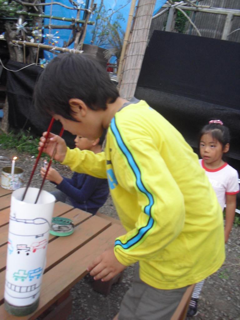 描いた絵は竹の土台に巻きつけて、火の点いたろうそくをいかに上手く入れられるかの練習をしています。