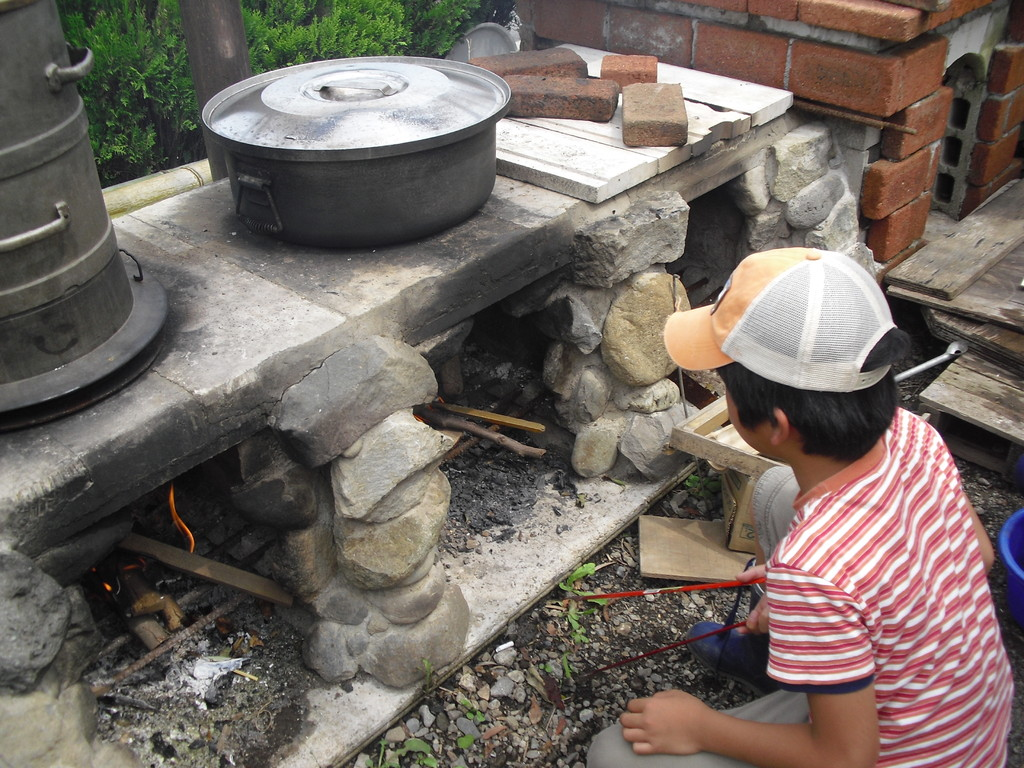 かまどでは大きな鍋にお湯を沸かしています。