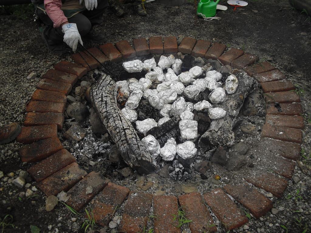 炭はいい具合に仕上がっています。その上に今包んだ食べ物を置いておきます。上手に焼けるかな?