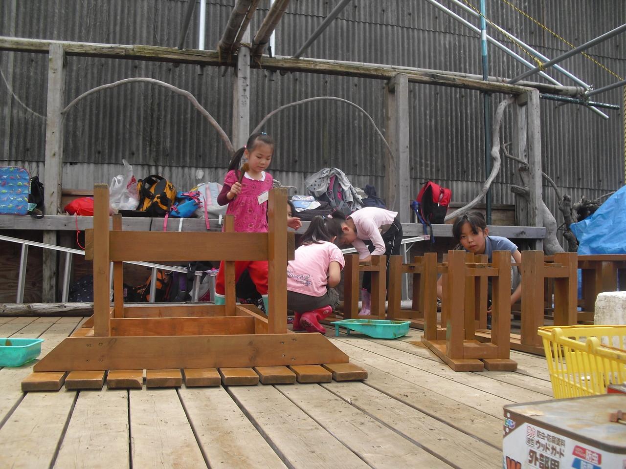 こちらはみんなで作ったテーブルと椅子に防腐剤を塗っています。