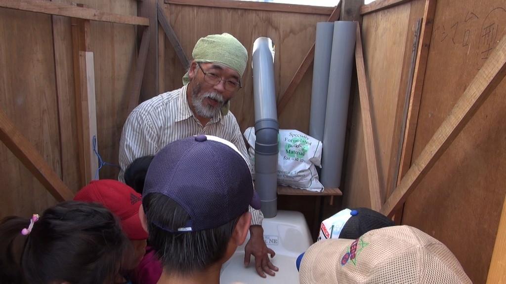 ニッセイ財団の助成金でいただいた、バイオトイレが備え付けられました。その使い方をみんなに教えているところなんです。