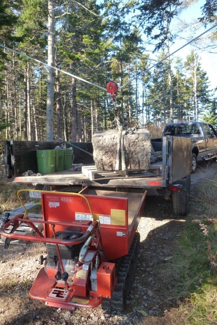Granite foundation stones are lifted from the trailer into the CanyCom toter with a skyline