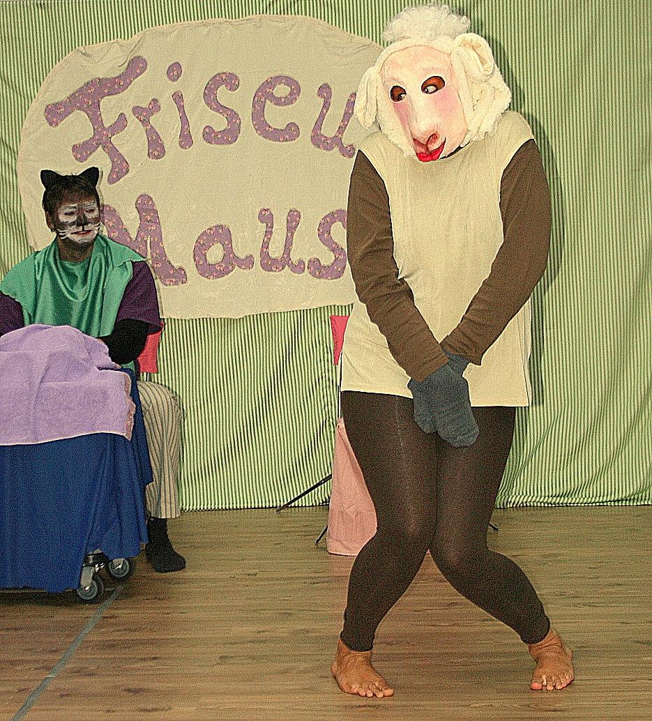 """Frau Schaaf wurde von Frisörmeisterin """"Frau Maus"""" geschoren, und schämt sich nun. Der Kater (im Hintergrund) ist amüsiert."""