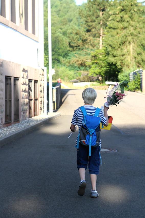 Zum letzten Mal: Auf dem Weg vom Auto an die Montessorischule trägt Henri auch die Fahne, die ihm seine Klassenlehrerin am Vortag geschenkt hat. Nicht zufällig ist es die niedersächsische: Zu Henris großer Freude ist ein weißes Pferd ist darauf ... :-)