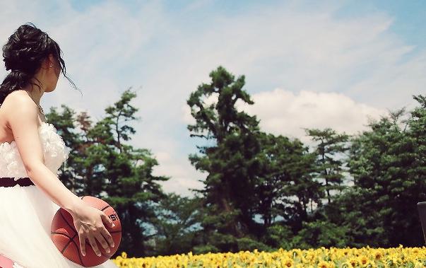 ひまわり畑を背景に趣味のバスケ。ボールを持つ新婦