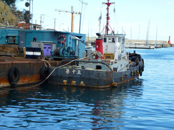神奈川県・真鶴漁港の工事船と赤い灯台