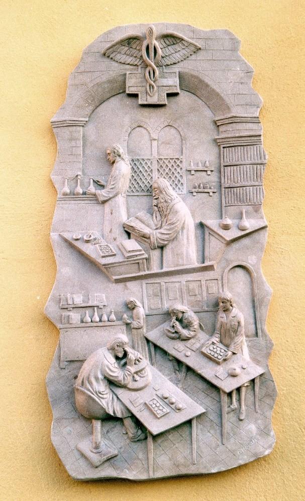 Il bassorilievo rappresenta due scene: sopra, un antico laboratorio con storte e alambicchi; sotto, un moderno laboratorio farmaceutico