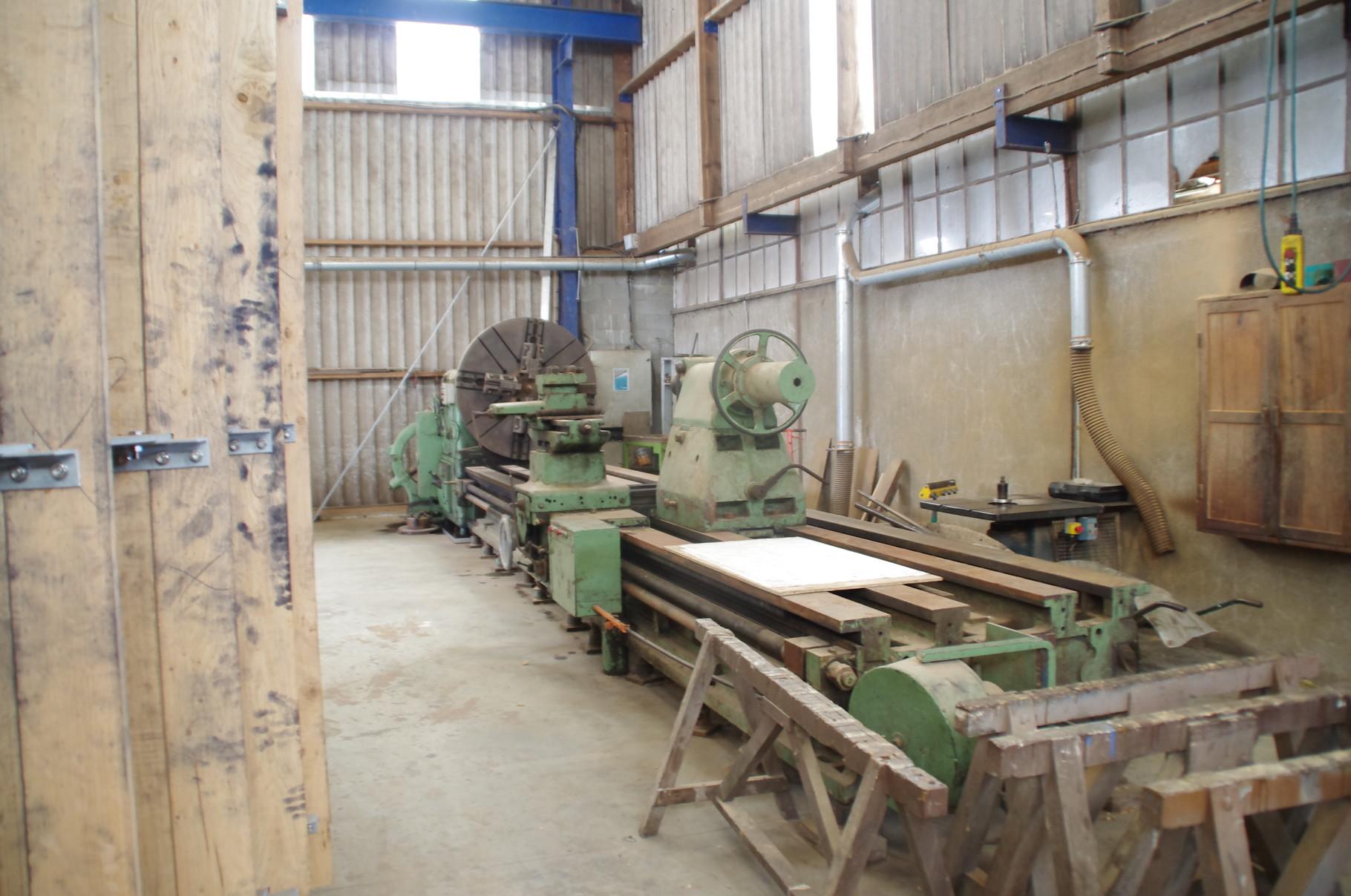 Le tour à bois pour le tournage d'axe de mouln à vent
